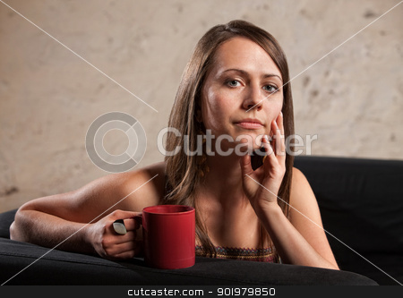 Thoughtful Lady with Cup stock photo, Thoughtful Caucasian brunette female sitting with mug on sofa by Scott Griessel