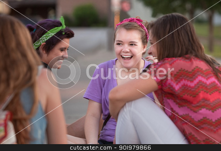 Four Teen Girls Giggling stock photo, Mixed group of four teenage girls outside giggling by Scott Griessel