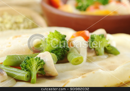 Crepe with Vegetables stock photo, Broccoli, mushrooms, beans, onions and pepper on pancake (Selective Focus, Focus on the broccoli, bean and mushroom in the front as well as the edge of the pancake in the right bottom corner) by Ildiko Papp