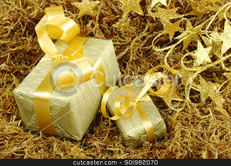Christmas Present stock photo, Boxes wrapped in golden paper with golden ribbon on brown moss with golden stars in the background (Selective Focus, Focus on front) by Ildiko Papp