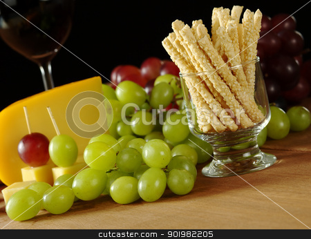 Sesame Sticks with Cheese and Grapes stock photo, Snack: Sesame sticks with white grapes, some red grapes, cheese and red wine in glass in the background on wooden board (Selective Focus, Focus on the sesame sticks) by Ildiko Papp