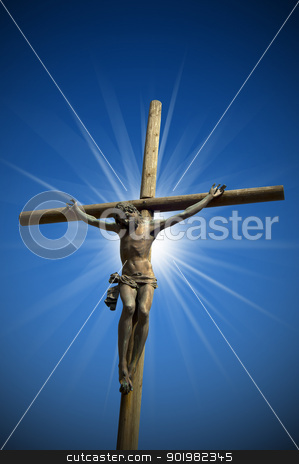 Crucifixion - The Jesus on the Cross stock photo, The cross (bronze and wood) - symbol of God's on blue sky  by catalby