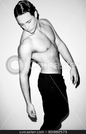 Portrait of a hunky muscular shirtless male model stock photo, Black and white portrait of a hunky muscular shirtless male model indoors by Ishay Botbol