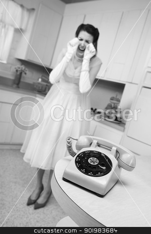 Woman Weeps By The Telephone stock photo, Young Caucasian woman weeps near a phone in a retro-style kitchen scene by Scott Griessel