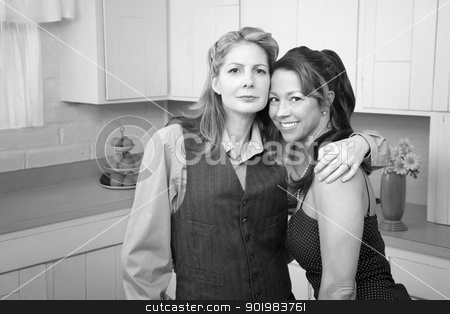 Girlfriends in a kitchen stock photo, Two middle-aged friends hug in a kichen by Scott Griessel