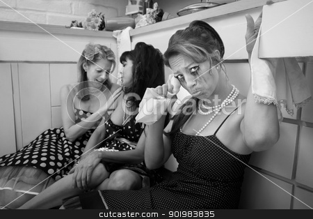 Weeping Woman stock photo, Weeping woman with friends wipes her tears with a napkin in kitchen by Scott Griessel