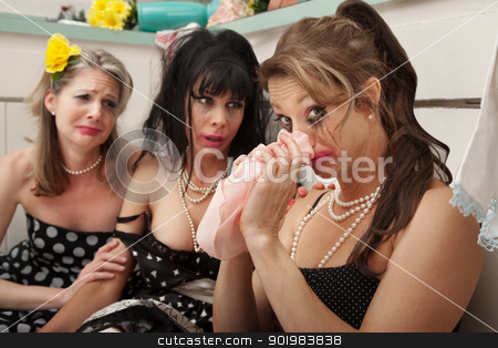 Weeping Woman  stock photo, Woman blows her nose while weeping friends look at her in the kitchen by Scott Griessel