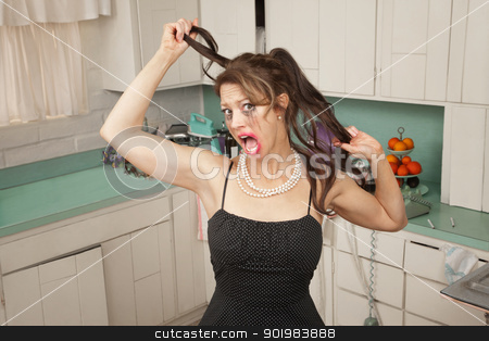 Woman Pulls Her Hair  stock photo, Screaming woman pulls her hair in a kitchen by Scott Griessel