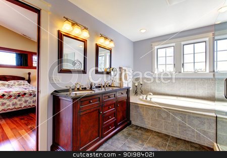 Nice lavendar bathroom with tub and wood cabinet with two sinks. stock photo, Nice lavendar bathroom with tub and wood cabinet with two sinks and tile floor. by iriana88w