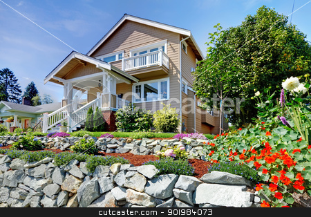 Two story beige nice house on the rocky hill with flowers. stock photo, Two story beige nice house on the hill with rock walls and flowers. by iriana88w