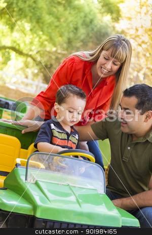 Young Mixed Race Boy Enjoys Toy Tractor with Parents stock photo, Happy Young Mixed Race Boy Enjoys A Toy Tractor While Parents Look On. by Andy Dean