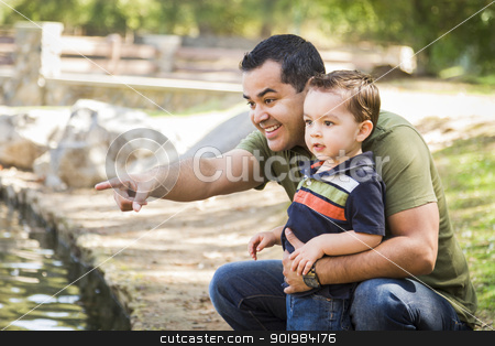 Hispanic Father Points with Mixed Race Son at the Park stock photo, Happy Hispanic Father Points with Mixed Race Son at the Park Pond. by Andy Dean