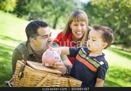 Mixed Race Couple Give Their Son a Piggy Bank at the Park stock photo, Happy Mixed Race Couple Give Their Son a Piggy Bank at a Picnic in the Park. by Andy Dean