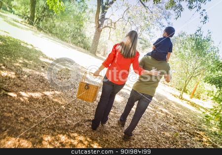 Mixed Race Family Enjoy a Walk in the Park stock photo, Happy Mixed Race Family with Picnic Basket Enjoy a Walk in the Park. by Andy Dean