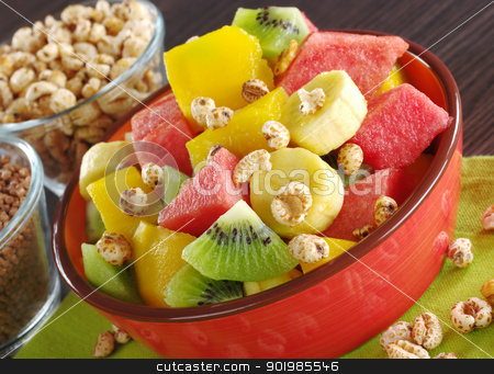 Fruit Salad with Cereals stock photo, Fresh fruit salad made of banana, kiwi, watermelon and mango pieces in orange bowl with cereals (puffed wheat and puffed chocolate quinoa) (Selective Focus, Focus on the front of the bowl and the fruits in the front) by Ildi Papp