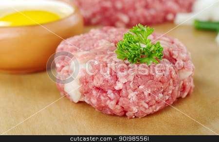 Raw Meatball stock photo, Raw meatball garnished with a parsley leaf and a raw egg, green onion pieces and mincemeat in the back (Very Shallow Depth of Field, Focus on the front of the meatball and the leaf) by Ildiko Papp