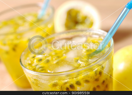 Passion Fruit Juice stock photo, Passion-fruit juice with icecubes and blue drinking straws with passion-fruits in the background on wood (Selective Focus, Focus on the front of the glass) by Ildiko Papp