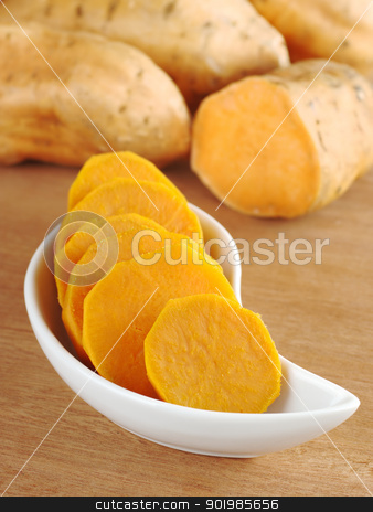 Cooked Sweet Potato Slices stock photo, Cooked sweet potato (lat. Ipomoea batatas) cut in slices in white bowl on wooden surface with sweet potatoes in the background (Selective Focus, Focus on the front of the bowl)  by Ildiko Papp