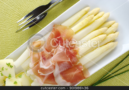 White Asparaus with Ham stock photo, Fresh cooked white asparagus served with ham and potatoes on long plate with chives and cutlery on the sides by Ildi Papp
