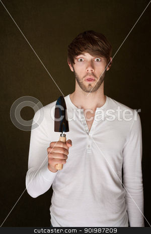 Shocked Man With Trowel stock photo, Shocked Caucasian man holding trowel on brown background by Scott Griessel