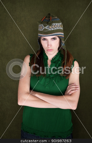 Frowning Woman stock photo, Woman with folded arms and sock monkey cap folds her arms by Scott Griessel