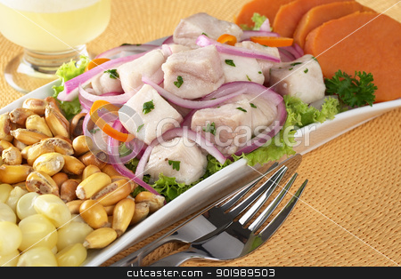 Peruvian-Style Ceviche stock photo, Peruvian-style ceviche made out of raw dogfish (Spanish: tollo), red onions and aji (Peruvian hot pepper) and served with corn, roasted corn (cancha) and sweet potato with Pisco Sour (Peruvian traditional cocktail) in the back (Selective Focus, Focus on the front of the fish) by Ildiko Papp