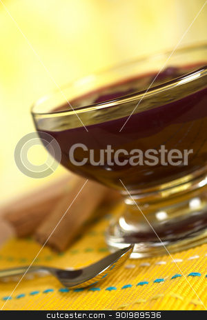 Peruvian Dessert Called Mazamorra Morada stock photo, Popular Peruvian dessert called Mazamorra Morada (made out of purple corn) with cinnamon sticks and spoon on the side (Selective Focus, Focus on the front of the bowl) by Ildi Papp