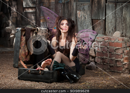 Worried Fairy stock photo, Worried Caucasian fairy with clothes sits in suitcase by Scott Griessel