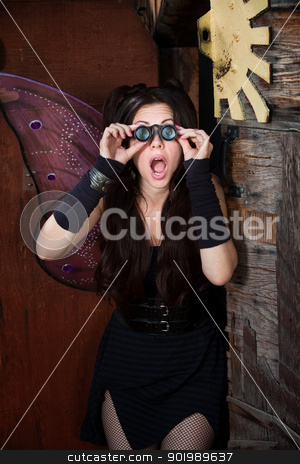 Surprised Fairy stock photo, Surprised pretty fairy looks through loupe glasses in rustic location by Scott Griessel