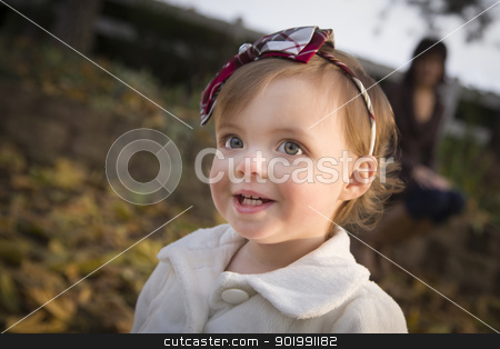 Adorable Baby Girl Playing in Park with Mom stock photo, Adorable Baby Girl Playing Outside in the Park with Mom Behind Her. by Andy Dean
