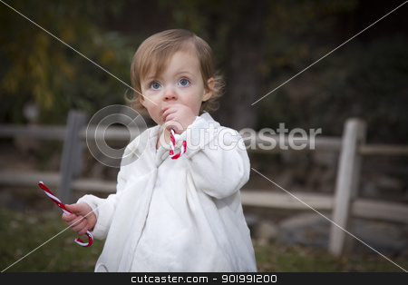 Adorable Baby Girl Playing in Park stock photo, Adorable Baby Girl Playing Outside in the Park with Candy Canes. by Andy Dean