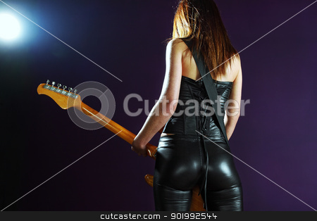 Sexy female playing an electric guitar stock photo, Photo of the back of a female guitar player standing and playing in front of a spotlight. by © Ron Sumners