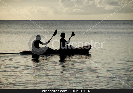 Kayakers silhouetted on the ocean stock photo, Man and woman silhouetted at sea in a kayak by Sarah Marchant