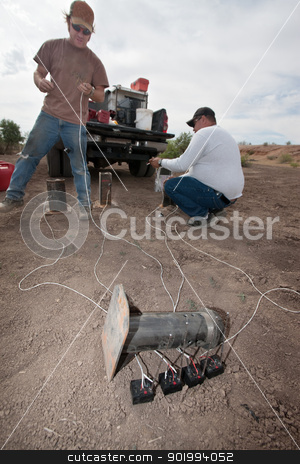 Two Movie Effects Men Working stock photo, Two men in special effects team near truck setting up explosives by Scott Griessel