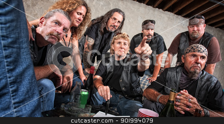 Biker Gang Lady Pointing stock photo, Tough female gang member with friends pointing ahead by Scott Griessel