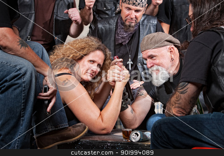 Serious Woman Arm Wrestling stock photo, Serious woman in arm wrestling contest with biker gang by Scott Griessel