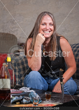 Smiling Woman with Knife Stuck in Table stock photo, Smiling middle aged woman in leather with dagger and alcohol by Scott Griessel
