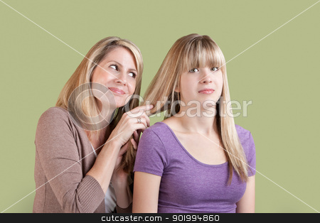 Over Involved Mother with Annoyed Daughter stock photo, Smiling Caucasian mom with annoyed daughter over green background by Scott Griessel