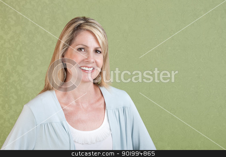 Smiling Woman stock photo, Mature Caucasian woman smiles over green background by Scott Griessel