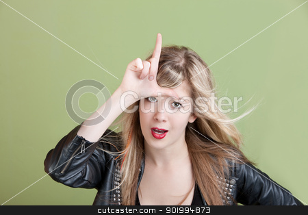 Loser Symbol stock photo, Young woman makes loser sign on her forehead over green background by Scott Griessel