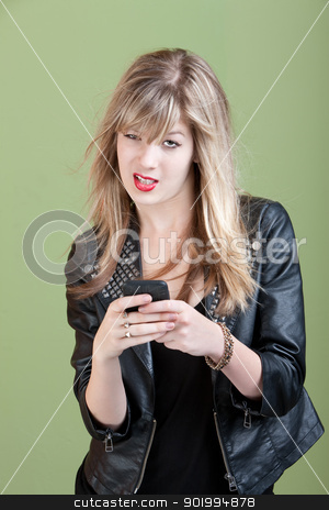 Annoyed Girl On Phone stock photo, Retro-styled young Caucasian lady types text message on her cellphone over green background by Scott Griessel