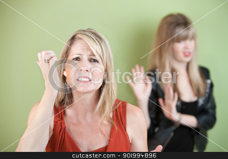Upset Mother and Daughter stock photo, Unhappy mother with frustrated daughter over green background by Scott Griessel