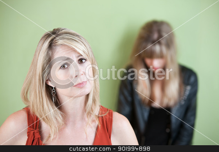 Worried Mother stock photo, Mother with embarrassed or sad daughter in background by Scott Griessel