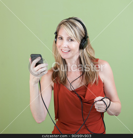 Woman Listens To Music stock photo, Middle-aged woman listens to music player over green background by Scott Griessel