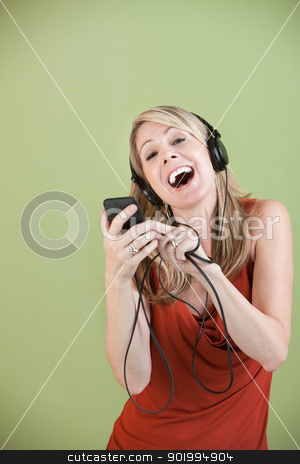 Lady Listens To Music stock photo, Mature Caucasian lady listens to music on headphones over green background by Scott Griessel