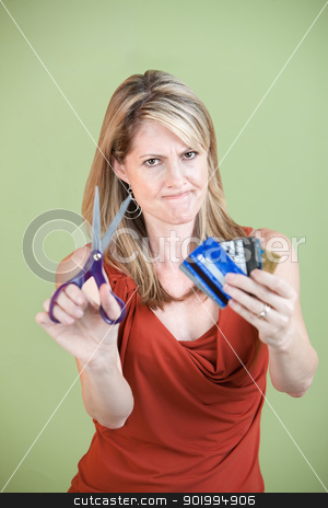 Woman Cuts Credit Cards stock photo, Upset mature woman ready to cut credit cards using scissors by Scott Griessel