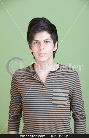 Skinny Latino Male stock photo, Serious young Hispanic man over green background by Scott Griessel