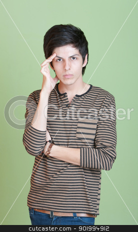 Upset Young Man stock photo, Young man over green background holds his head by Scott Griessel