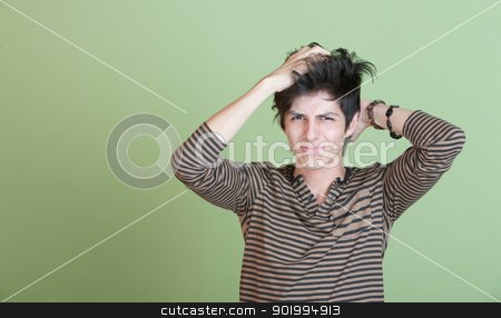 Confused Teen stock photo, Young man over green background puts hands through hair by Scott Griessel