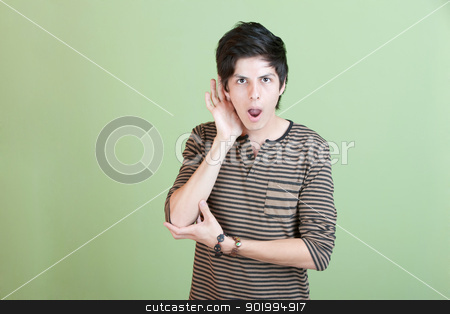 Surprised Young Man stock photo, Shocked young man with hand on ear over green background by Scott Griessel
